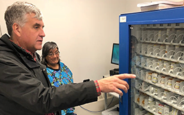 "Deputy Secretary Eric Hargan looks at a medicine ""vending machine"""
