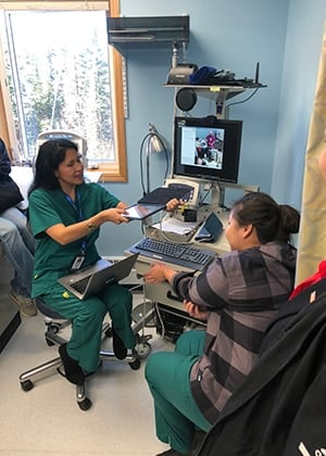 In Hughes, Alaska a community health aide use an online diagnostic tool to examine a patient with a rash and consult on treatment approaches through a two-way internet connection with a physician assistant and a pharmacist in Fairbanks.